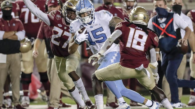 UNC receiver Beau Corrales (15) makes a catch over Florida State's Akeem Dent (27) and Travis Jay on Saturday during the Tar Heels' rally that came up just short in Tallahassee. They try to stay away from a losing streak this week against archrival NC State.