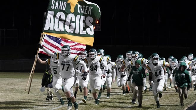 The Sand Creek football team takes the field at Addison for the Division 8 district championship game.