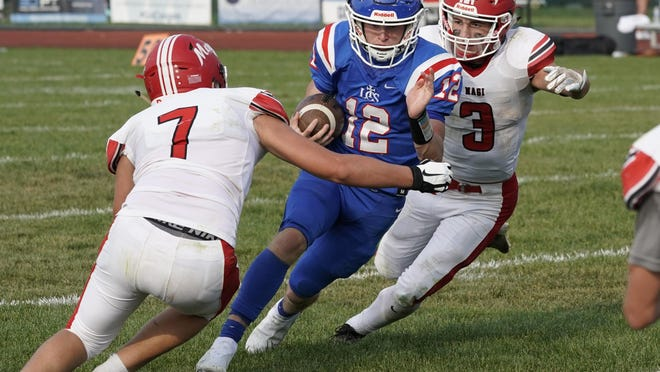 Lenawee Christian quarterback Landon Gallant (12) rushes as a pair of Colon defenders close in to try to bring him down during their game on Saturday afternoon at Cougar Field in Adrian.