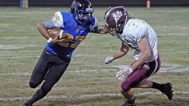 Madison's Mario Garcia (27) stiff arms Morenci's Rodney Zimmerman as he runs with the ball during the first half of Friday's Tri-County Conference game at Madison.