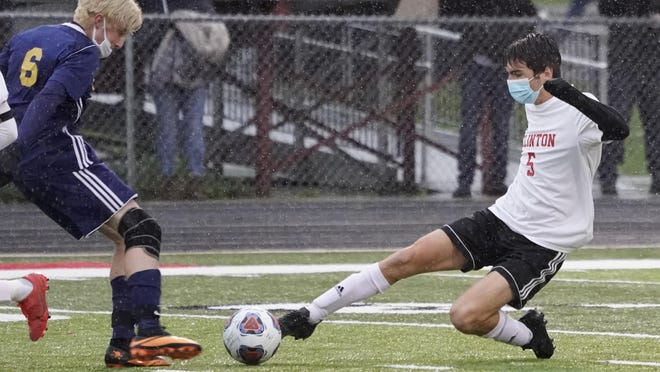 Clinton senior defender Nate Chavez (5) lunges for the ball as Clawson's Tyler Harvill (6) during Tuesday night's Division 3 regional semifinal at Livonia Clarenceville High School.