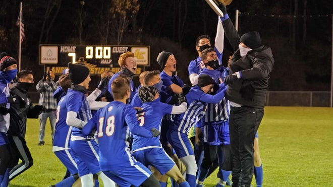 The Lenawee Christian boys soccer team celebrates with head coach Nate Sharpe, right with trophy, after winning their Division 4 regional final game against Hillsdale Academy 7-0 on Friday night at Lansing Christian.