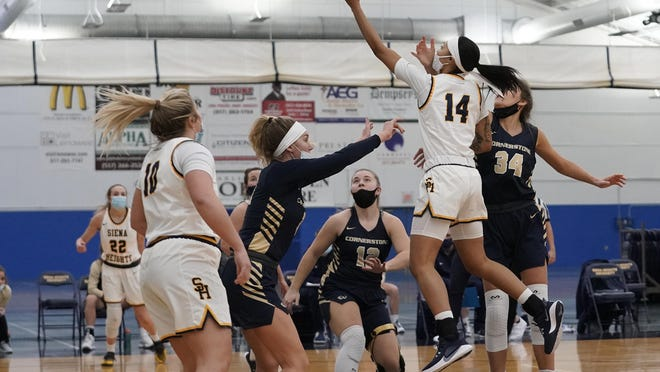 Siena Heights sophomore guard Sha'kyia Parker (14) shoots a layup over a Cornerstone defender during Wednesday night's Wolverine-Hoosier Athletic Conference game at the SHU Fieldhouse.