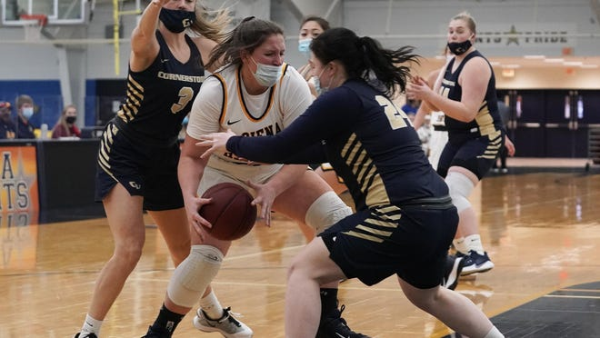 Siena Heights' Peyton Banks battles with the ball against two Cornerstone defenders during Wednesday's game.