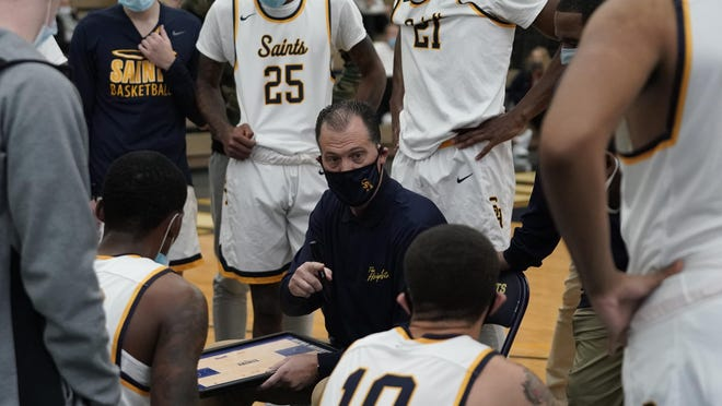 Siena Heights head coach Joe Pechota draws up a play during a timeout in Wednesday's game against Cornerstone.