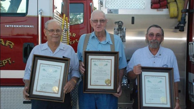 Troy Warlick (center) died last week after years of service to the community. In 2017, he was awarded the Order of the Long Leaf Pine with fellow firefighters James McNeily (right) and Dewey Cook (left).