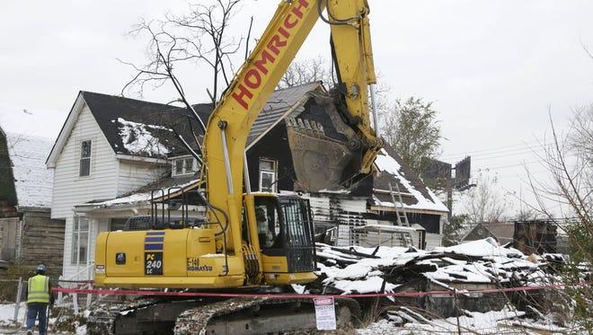 A house on Lyon Street in southwest Detroit is torn down in November 2015.