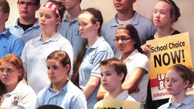 Calvary Christian School students hold signs supporting vouchers and school choice as they stand at the front of the school's auditorium, which Gov. Mike Pence visited to sign House Enrolled Act 1003, expanding vouchers, in May 2013.