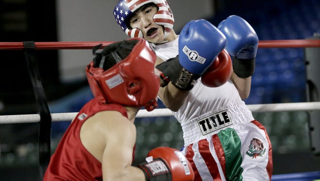 Jorge Monclova hits Luis Angel Ledesma with an upper cut during their bout Saturday in the El Paso Regional Golden Gloves at the El Paso County Coliseum.