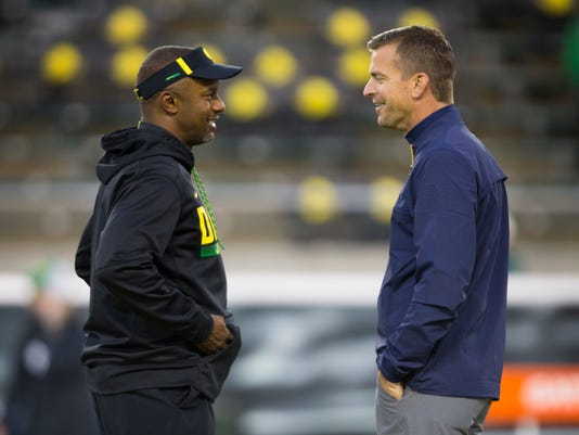 Oregon head coach Willie Taggart, left, talks with California head coach Justin Wilcox before their NCAA college football game Saturday, Sept. 30, 2017, in Eugene, Ore. (AP Photo/Chris Pietsch)