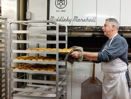 Gino Baldino takes a tray of paczki pastries out of