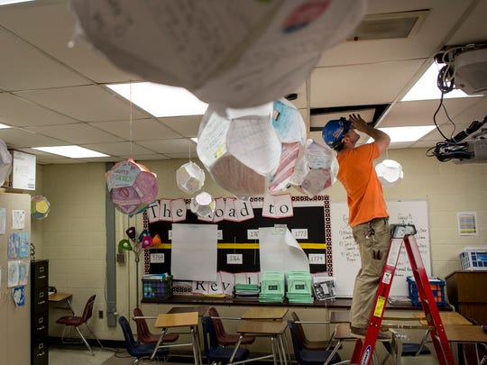 Contractor Andrew Allemon removes tiles from a ceiling