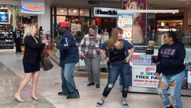 Chelsea White (left) encounters a flash mob while Christmas shopping at Westfield Palm Desert. The mob was organized as part of a wedding proposal organized by Edward's boyfriend, Cody White.
