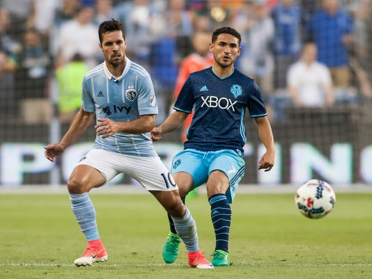 Sporting Kansas City midfielder Benny Feilhaber (10) passes the ball away from Seattle Sounders midfielder Cristian Roldan (7) during an MLS soccer match Wednesday, May 17, 2017, in Kansas City, Kan. (Nick Tre. Smith/The Kansas City Star via AP)