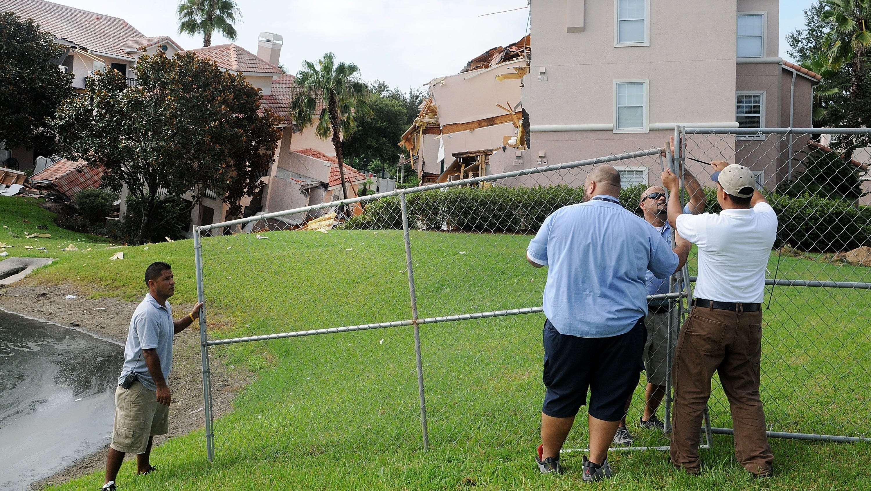 Employees install a fence around the building that partially collapsed into a sinkhole at Summer Bay Resort.