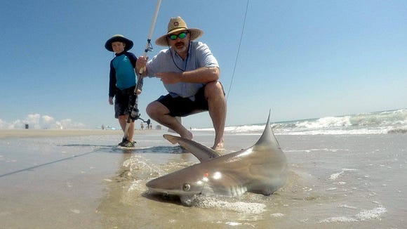 Jonathan Kline with a shark he caught and released in the Brigantine surf.