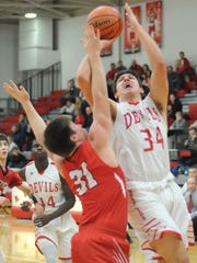 West Side sophomore George Karlaftis grinds his way to the basket past Attica's Federico Montes Tuesday night.