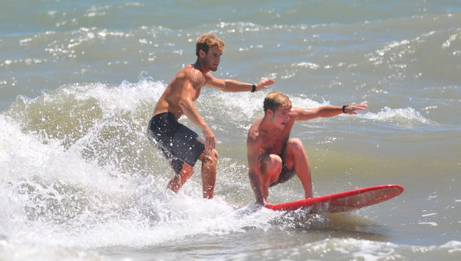 Corey Howell and Sam Duggan clowning around doing some tandem surfing. Scenes from the National Kidney Foundation Pro/Am Rich Salick Surf Festival in Cocoa Beach Saturday.