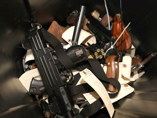 A bin collecting handguns is pictured during the gun