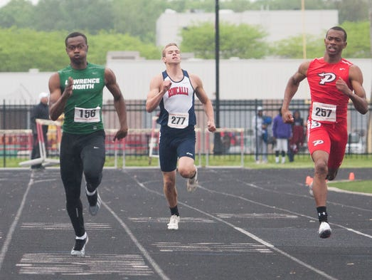L-R Keenen Johnson, Lawrence North, Ryan Hume, Roncalli, and Adrian Robinson, Pike, run a preliminary heat of the 200 meter dash at the Boys Marion County Track Meet at North Central High School.