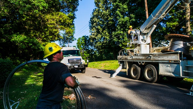 May 31, 2017 - MLGW employee Mark McGoff rolls primary wire to add to a pole with colleague Miguel Calderon as they work along Point Church Ave. in Frayser on Wednesday afternoon. A storm swept through Memphis late on Saturday night causing thousands of MLGW customers to be without power.