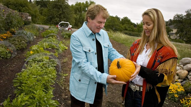 Danny Wegman presents his wife Stency with a pumpkin he picked while touring at the Wegmans organic farm in Canandaigua in 2007.