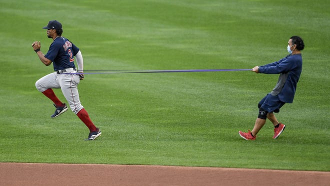 Boston Red Sox shortstop Xander Bogaerts, left, warms up before a baseball game against the Toronto Blue Jays in Buffalo, N.Y., Wednesday, Aug. 26, 2020.