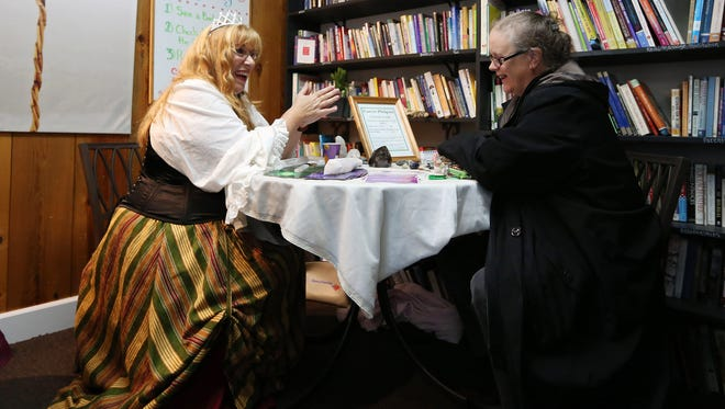 Crystal guide Carrie Philpott, left, identifies two crystals for Sheri Gomez of Salem during a Halloween/anniversary/psychic fair Sunday, Oct. 25, 2015, at Journeys...A Center for Your Soul in Salem, Ore.