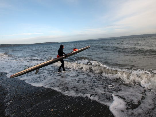 Steve Rhoades walks into the surf with his paddleboard
