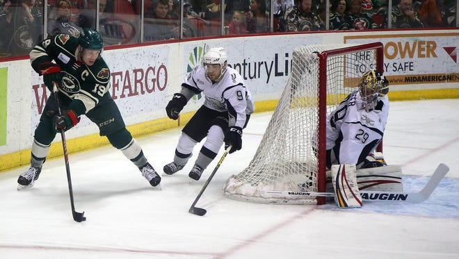 Iowa Wild left wing Stephane Veilleux moves the puck around San Antonio center Rocco Grimaldi as goalie Michael Houser watches from inside his net on Friday, March 27, 2015, at Wells Fargo Arena in Des Moines, Iowa.