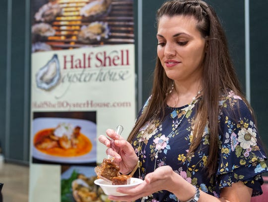 Megan Ezell tries a local delicacy at the 14th Annual Taste of Acadiana at the Cajundome on July 25, 2018. Events like this food showcase can bring in vendors and visitors to the arena and region.