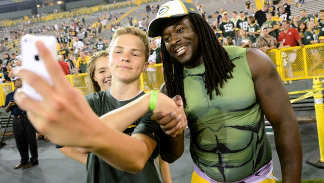 Noah Steward, 14, takes a 'seflie' with running back Eddie Lacy after the Family Night practice at Lambeau Field on Saturday, Aug. 2, 2014.