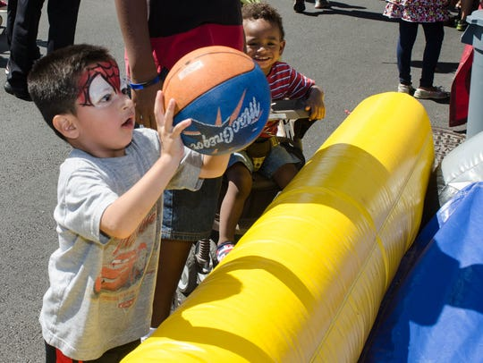 Christian Herrera, 4, tries his luck at basketball