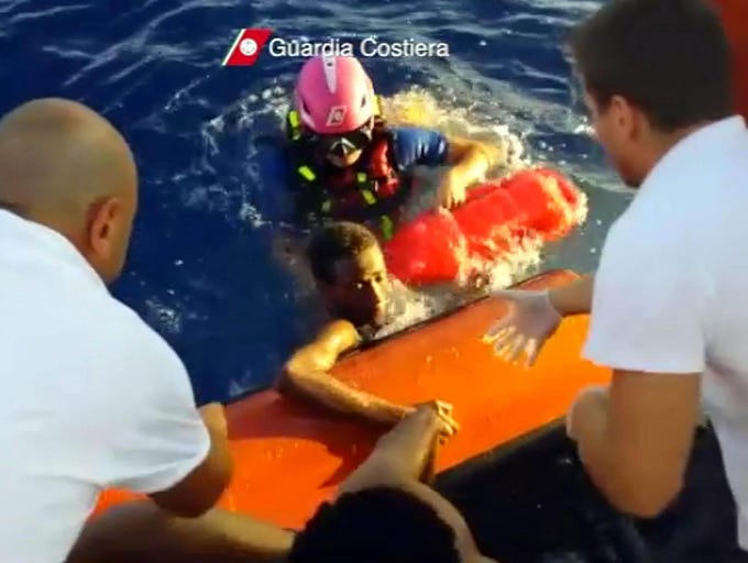 A person is helped onto a coast guard vessel after a migrant boat caught fire and sank on Oct. 3 near Lampedusa Island, Italy. One hundred fourteen people were killed and 200 are still missing after the vessel carrying over 500 migrants sank.