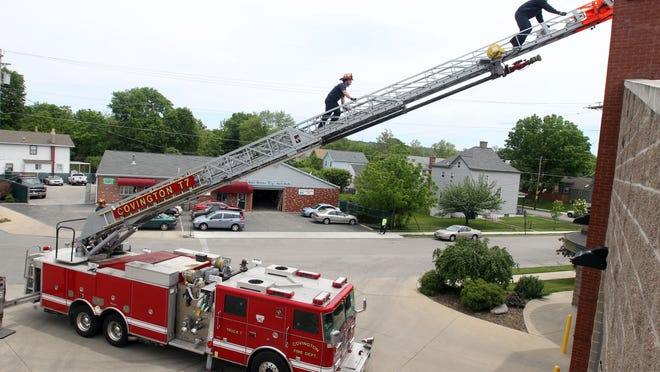 Covington firefighters Zack Williams, right, and Brian Grady climb the aerial ladder at Company 8 in Latonia. As part of routine checks, they pull the truck from the station and extend the ladder to ensure everything is in working order. The city is considering closing a ladder truck and ambulance at Company 8 and moving the personnel to a station in the northern part of the city.