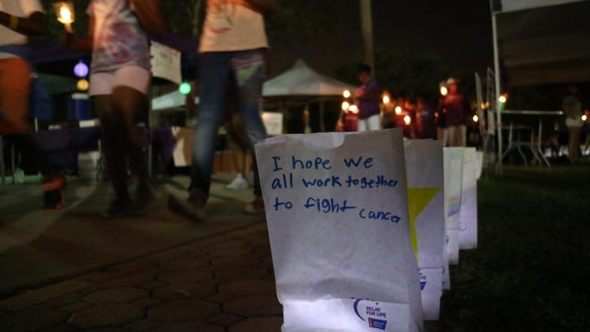 Volunteers holding candles take a silent lap around luminaria bags at last year's Relay for Life of Northern Palm Beach County at Abacoa in Jupiter.