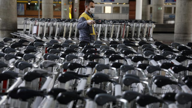 A worker disinfects trollies at terminal of Tehran's Imam Khomeini airport, Iran, Friday, July 17, 2020. The first Emirates flight arrived in Iran after nearly 5 months of suspension of the most airliners flights to the country due to the coronavirus outbreak, as Iranian officials at the airport say they are doing everything possible to ensure passengers are not infected, and isolate those with symptoms.