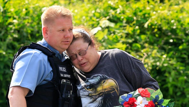 Kansas City, Kan., police officer Brad Lightfoot, left, consuls Susan Goble at the shooting scene of a police officer in Kansas City, Kan., Tuesday, July 19, 2016. Goble knows the family of the fallen officer and hoped to place a wreath near the site of the shooting.  A suspect in a drive-by shooting fatally shot Capt. Robert Melton, a 17-year veteran of the Kansas City, Kan., Police Department, on Tuesday as the officer was sitting in his patrol car, police said.