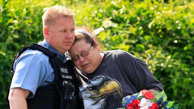 Kansas City, Kan., police officer Brad Lightfoot, left, consoles Susan Goble at the shooting scene of a police officer in Kansas City, Kan., Tuesday, July 19, 2016.