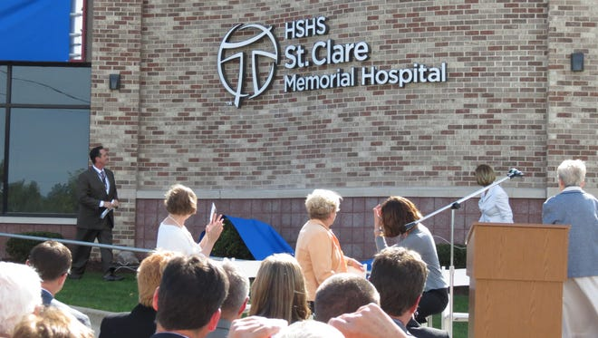 Dan DeGroot, chief operating officer for HSHS St. Clare Memorial Hospital in Oconto Falls, and Therese Pandl, president and CEO of the Eastern Wisconisn Division of HSHS, look at the new sign of the hospital after unveiling it on Sept. 3.