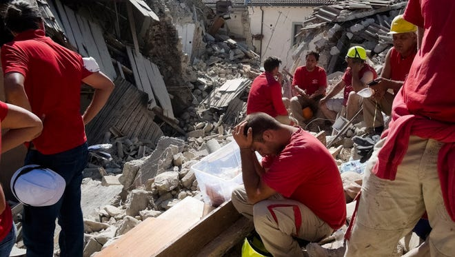 Rescuers pause in Amatrice, central Italy, where an earthquake struck just after 3:30 a.m., Wednesday, Aug. 24, 2016. The quake was felt across a broad section of central Italy.