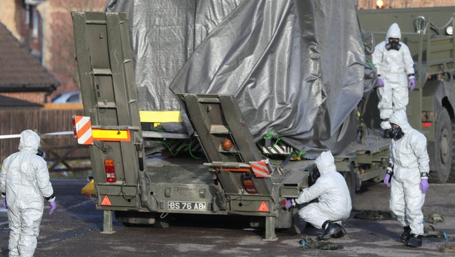 Investigators in protective clothing move a wrapped ambulance from the South Western Ambulance Service station in Harnham, near Salisbury, England, as police and members of the armed forces probe the suspected nerve agent attack on Russian spy double agent Sergei Skripal, Saturday.