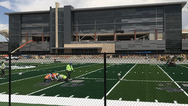 Workers stitch yard-line numerals into the artificial turf field at CSU's new football practice facility adjacent to the on-campus stadium.