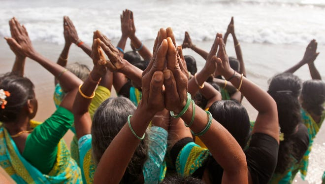 Indian women offer prayers on the Marina Beach at the Bay of Bengal on Dec. 26, 2014.