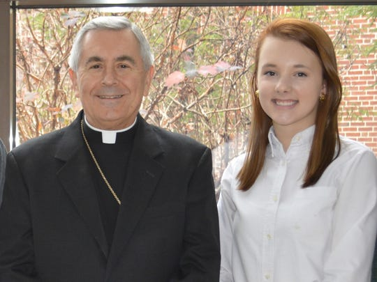 Delone Catholic High School student Kristen Landsman stands with Bishop Ronald Gainer at a luncheon for the winners of the Diocese of Harrisburg's Christmas Card Contest.