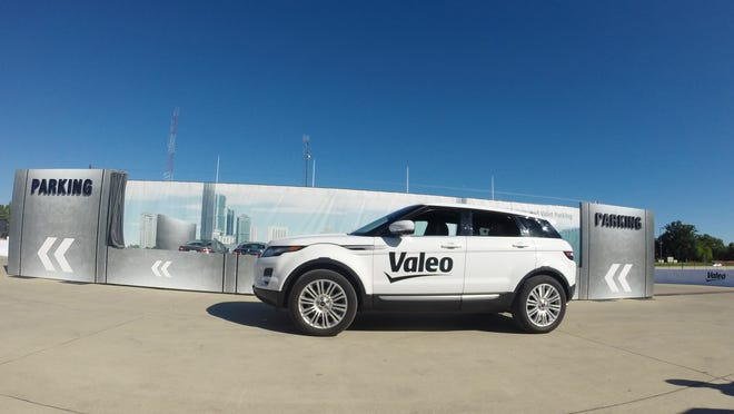 A Range Rover drives by itself toward a parking spot during a demonstration Monday by Valeo in Detroit. Technology being honed by the French auto parts maker uses a dozen ultrasonic sound-wave sensors, 360-degree cameras and a laser scanner.