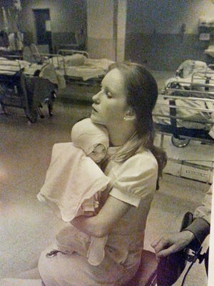 In this 1977 photo provided by Albany Medical Center, nurse Susan Berger cuddles infant Amanda Scarpinati, who had been severely burned by a steam vaporizer at home, in the pediatric unit at Albany Medical Center in Albany N.Y. Scarpinati kept the hospitalís annual report that published the photo and was comforted by the picture when she was bullied for her burn scars as a child. She recently used social media to learn Bergerís identity so she could thank her for her loving care.