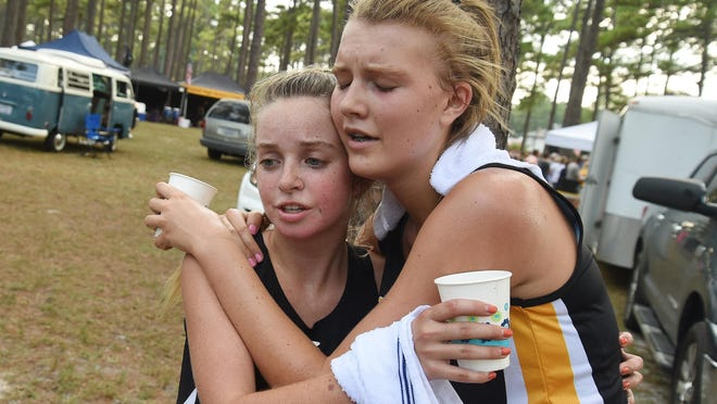 Paxton Chitty (left) is congratulated by friend and competitor Makayla Obremski after Chitty won the 2018 Wilmington Cross Country Kickoff. In July, the duo separately committed to East Carolina University.