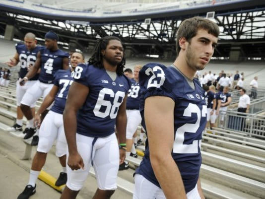 Penn State safety Ryan Keiser (23) departs the bleachers with his teammates Thursday after the team photo was taken at media day in State College. (DAILY RECORD/SUNDAY NEWS - CHRIS DUNN)