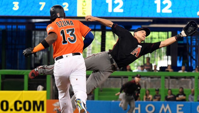Nick Ahmed #13 of the Arizona Diamondbacks reaches for a throw from Paul Goldschmidt #44 on a double play attempt in the third inning against the Miami Marlins at Marlins Park on June 4, 2017 in Miami, Florida.